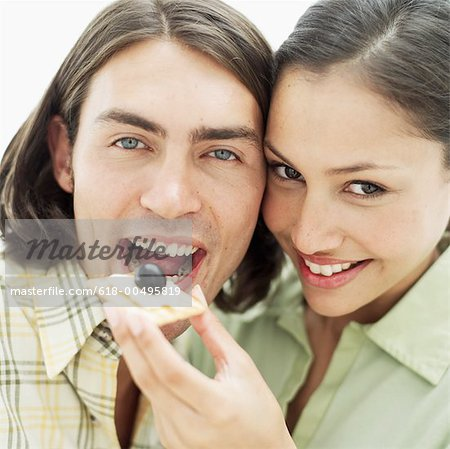 close-up of a young woman feeding a cracker with cheese to a young man Stock Photo - Premium Royalty-Free, Image code: 618-00495819
