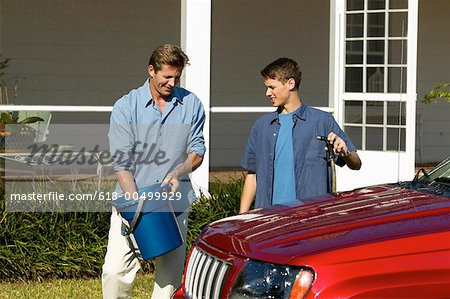 Father and teenage son (18-20) washing a car together Stock Photo - Premium Royalty-Free, Image code: 618-00499929