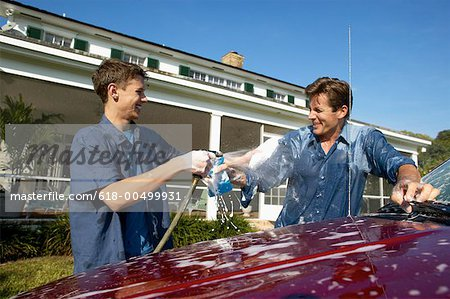 Father and teenage son (18-20) washing a car together Stock Photo - Premium Royalty-Free, Image code: 618-00499931