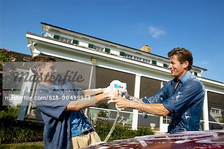 Father and teenage son (18-20) washing a car together Stock Photo - Premium Royalty-Free, Image code: 618-00499933