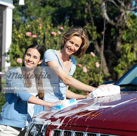 Portrait of a mother and teenage daughter (17-18) washing the car Stock Photo - Premium Royalty-Free, Image code: 618-00499947