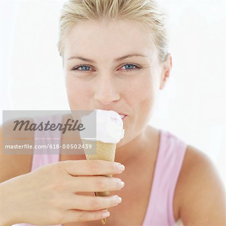 Young woman eating an ice cream cone Stock Photo - Premium Royalty-Free, Image code: 618-00502439