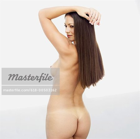 rear view of a naked young woman with her hands above her head Stock Photo - Premium Royalty-Free, Image code: 618-00503162