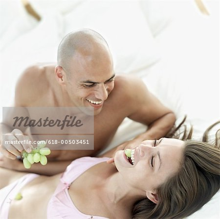 portrait of a young man feeding grapes to a woman lying down Stock Photo - Premium Royalty-Free, Image code: 618-00503451