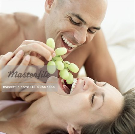 man feeding a woman grapes in bed Stock Photo - Premium Royalty-Free, Image code: 618-00503454