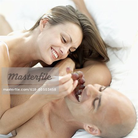 Young woman feeding a young man grapes in bed Stock Photo - Premium Royalty-Free, Image code: 618-00503458