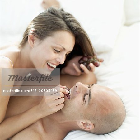 A young woman lying on top of A young man feeding him grapes Stock Photo - Premium Royalty-Free, Image code: 618-00503459