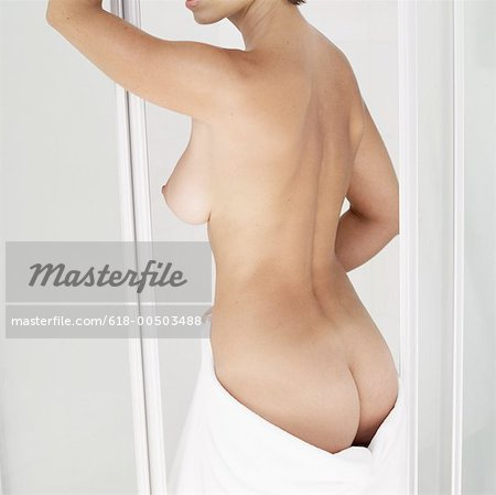 rear view of a woman with a towel around her waist Stock Photo - Premium Royalty-Free, Image code: 618-00503488