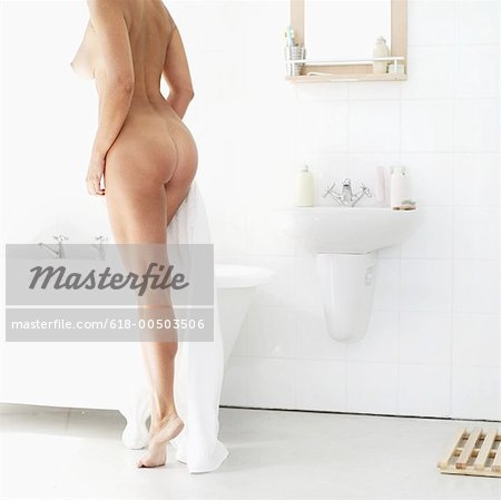 rear view of a naked woman stepping into a bathtub Stock Photo - Premium Royalty-Free, Image code: 618-00503506
