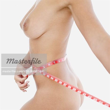 side profile of a naked woman measuring her waist Stock Photo - Premium Royalty-Free, Image code: 618-00503541