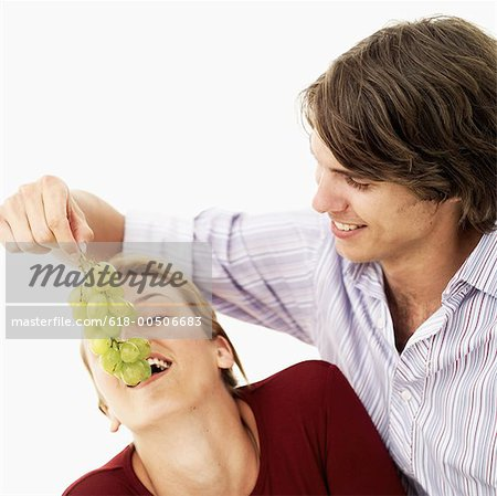 Young man feeding grapes to a Young woman Stock Photo - Premium Royalty-Free, Image code: 618-00506683