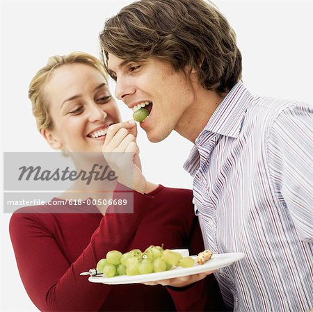 close-up of a young woman feeding grapes to a young man Stock Photo - Premium Royalty-Free, Image code: 618-00506689