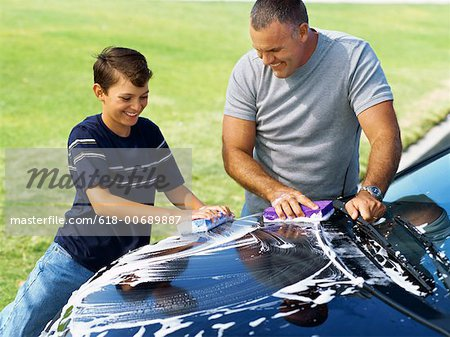 high angle view of a father and his son washing a car Stock Photo - Premium Royalty-Free, Image code: 618-00689887