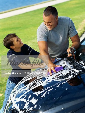 high angle view of a father and his son washing a car Stock Photo - Premium Royalty-Free, Image code: 618-00689888