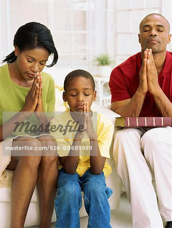 parents and their son praying
