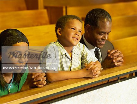 parents and their son praying in church Stock Photo - Premium Royalty-Free, Image code: 618-00690074