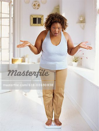 portrait of a mid adult woman standing on a weighing scale Stock Photo - Premium Royalty-Free, Image code: 618-00690838