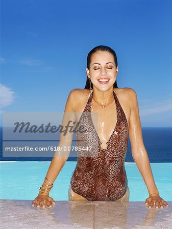Young woman with her eyes closed emerging from a pool Stock Photo - Premium Royalty-Free, Image code: 618-00785447