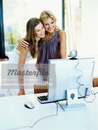Mother and her daughter standing in front of a video conference camera on a computer monitor Stock Photo - Premium Royalty-Free, Image code: 618-00830788