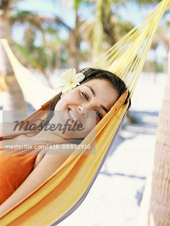 Side view of a young woman lying on her back in a hammock Stock Photo - Premium Royalty-Free, Image code: 618-00832910