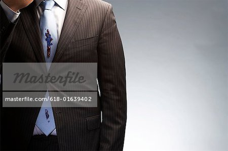 Businessman wearing jacket buttoned with only one button, mid section Stock Photo - Premium Royalty-Free, Image code: 618-01639402