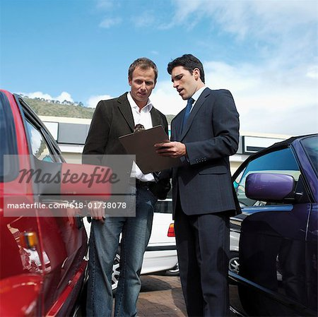 Car salesman talking with customer, standing between two cars outdoors Stock Photo - Premium Royalty-Free, Image code: 618-01738078
