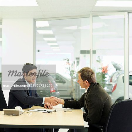Car salesman shaking hands over desk with customer in car showroom Stock Photo - Premium Royalty-Free, Image code: 618-01738079