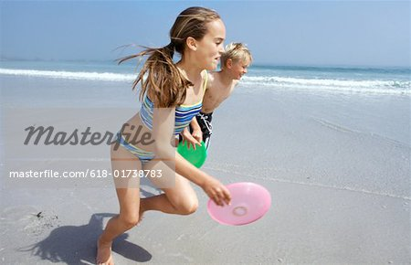 Boy and girl (11-13) running with flying disc on beach Stock Photo - Premium Royalty-Free, Image code: 618-01738783