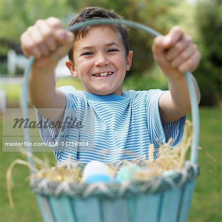 Boy (8-9) holding basket of eggs, outdoors, portrait Stock Photo - Premium Royalty-Free, Image code: 618-01738904
