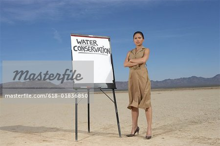 Businesswoman beside sign stressing water conservation Stock Photo - Premium Royalty-Free, Image code: 618-01836850