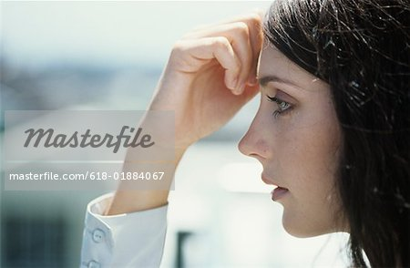 Young woman with hand on forehead outdoors,close-up,profile Stock Photo - Premium Royalty-Free, Image code: 618-01884067