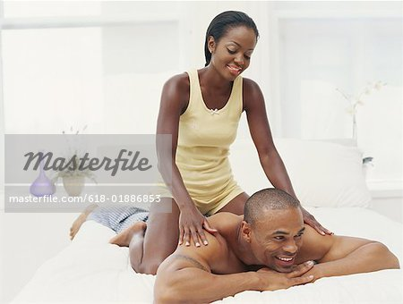 Young couple in bedroom, woman massaging man, smiling Stock Photo - Premium Royalty-Free, Image code: 618-01886853