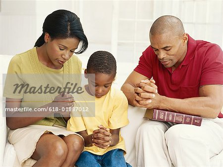 Parents with son (6-9) praying Stock Photo - Premium Royalty-Free, Image code: 618-01887012