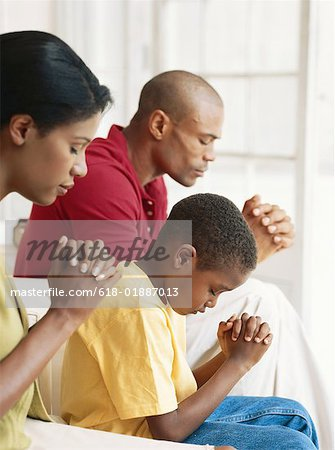 Parents with son (6-9) praying, side view Stock Photo - Premium Royalty-Free, Image code: 618-01887013