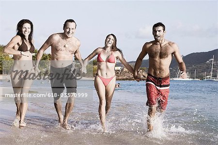 Two mid adult couples holding hands and running on the beach Stock Photo - Premium Royalty-Free, Image code: 618-03570999