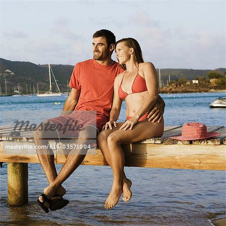 Mid adult man with his arm around a mid adult woman and sitting on a jetty Stock Photo - Premium Royalty-Free, Image code: 618-03571004