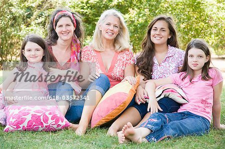 Portrait of two mature women sitting in a park with their daughters and smiling Stock Photo - Premium Royalty-Free, Image code: 618-03572341