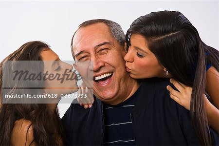 Grandfather being kissed by granddaughters, Stock Photo - Premium Royalty-Free, Image code: 618-03573793