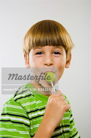 Young Boy Enjoying Green Lollipop Stock Photo - Premium Royalty-Free, Image code: 618-03610034