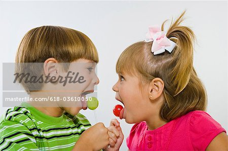 Boy and girl enjoying green and red lollipops Stock Photo - Premium Royalty-Free, Image code: 618-03610050