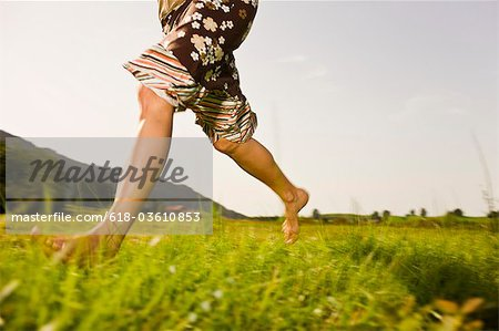Woman running barefoot through grass, low section Stock Photo - Premium Royalty-Free, Image code: 618-03610853