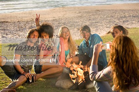 Friends around campfire at beach posing for photograph Stock Photo - Premium Royalty-Free, Image code: 618-03610886