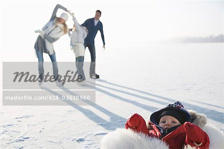 Family playing on ice with son wrapped in fur in foreground Stock Photo - Premium Royalty-Free, Image code: 618-03610960