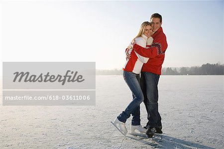 Portrait of couple embracing on ice, smiling Stock Photo - Premium Royalty-Free, Image code: 618-03611006