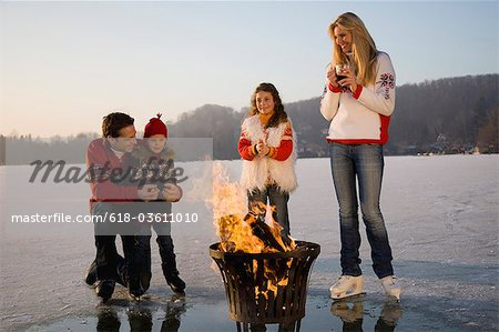 Young family around bonfire on ice, smiling Stock Photo - Premium Royalty-Free, Image code: 618-03611010