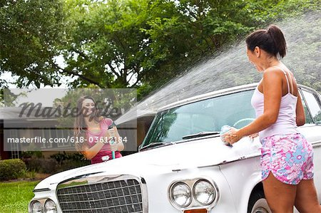Mother daughter washing car Stock Photo - Premium Royalty-Free, Image code: 618-03612184