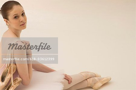 A young ballerina with ballet shoes draped over her shoulder Stock Photo - Premium Royalty-Free, Image code: 618-03612399