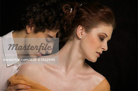 A young couple, man kissing woman's shoulder Stock Photo - Premium Royalty-Free, Image code: 618-03612445