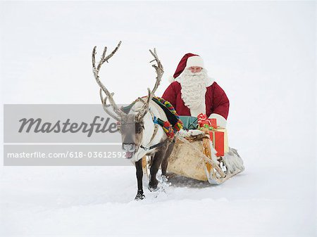 A reindeer pulling Santa Claus and his sleigh of presents Stock Photo - Premium Royalty-Free, Image code: 618-03612592