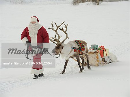 Santa Claus leading his reindeer and sleigh through the snow Stock Photo - Premium Royalty-Free, Image code: 618-03612594